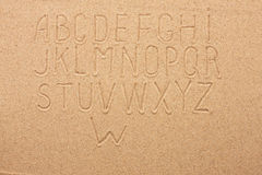 English, German, Portuguese alphabet  written on the sand Royalty Free Stock Photography