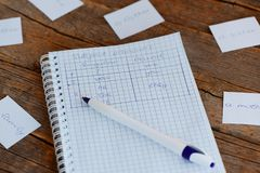 Learning English. A notebook, a pen, cards with words on a wooden table. Studying subject pronouns. Basic English grammar Stock Photos