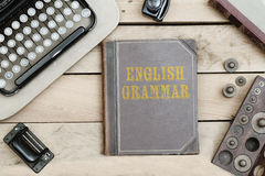 English Grammar on old book cover at office desk with vintage it Stock Images
