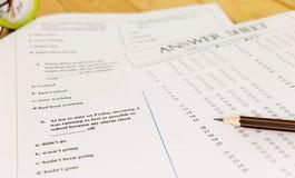 English grammar test sheet. On wooden desk Royalty Free Stock Photo