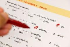 English grammar test sheet. On wooden desk Stock Photos