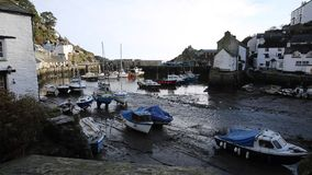 English harbour Polperro Cornwall England UK out of season in winter with boats at low tide stock footage