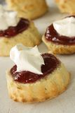 English Jam Scones. English scones topped with jam and whipped fresh cream stock image
