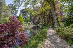 An English landscape garden in Spring with a path going around a pond. Tranquil pond in an English landscape garden in Spring Stock Photography