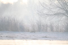 English landscape in winter with fox barely visible through the mist. Wintry landscape, with frost, mist and a red fox just visible through the mist. Icy water Stock Photo