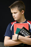English language learner. Portrait of a young teenage boy holding his school English language books. Black background Royalty Free Stock Photos