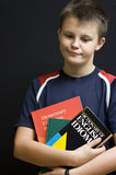 English language learner. Portrait of a young teenage boy holding his school English language books, making funny face. Black background Royalty Free Stock Image