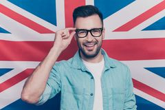 English language learning concept-portrait of cheerful man with. Bristle holding his hand on glasses standing over English flag background royalty free stock photo