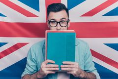 English language learning concept-portrait of excited man holdin. G colorful copy books in hands closing half face with notebooks standing over English flag Stock Images