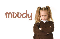 English language learning vocabulary school card with word moody and sweet young schoolgirl. With blond hair and folded arms angry and upset frustrated and Stock Images