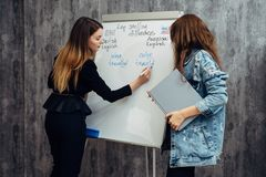 English language school. Two female students talking in classroom. stock images