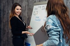 English language school. Two female students talking in classroom. stock photos