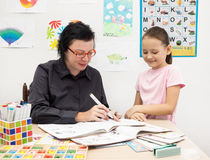 English language teacher with child checks notebook Royalty Free Stock Images