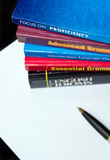 English learning levels. English language textbooks piled up and blank sheet of paper with pen. Levels of proficiency concept Royalty Free Stock Photography
