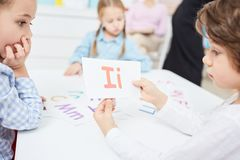 English lesson. Clever little kids learning english alphabet at lesson, boy showing paper card with letter I Royalty Free Stock Images