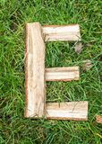 English letter from alphabet made from natural oak. On the grass stock images