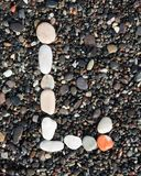 Letters alphabet laid on a black sand. L. English letters of alphabet laid on a black sand. L royalty free stock photo
