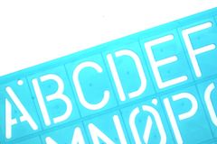 English Letters Plastic Stencils Alphabet. Isolated on White Background stock photo