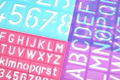 English Letters Plastic Stencils Alphabet. On White Background stock photos
