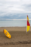 English lifeguard yellow board nd red and yellow flag on beach Stock Images