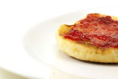 English Muffins. Lightly toasted sourdough english muffins with butter and strawberry preserves on white background Royalty Free Stock Images