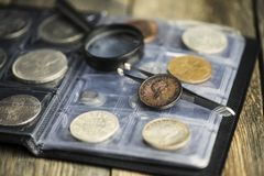 English old coin, magnifier and tweezers, numismatics. On old wooden background stock images