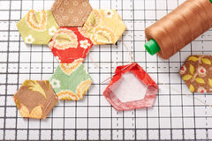 English paper pieced hexagons on white craft mat Royalty Free Stock Photo