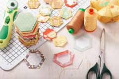 English paper pieced hexagons on white craft mat. Sewing equipment Royalty Free Stock Photos