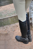 English Riding Boots. A person wearing English riding boots standing against a wood fence on a dirt ground Royalty Free Stock Photos