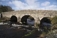 English river with old stone bridge on Dartmoor England UK. The East Dart River and road bridge built in the 1700`s at Postbridge on Dartmoor in Devon England UK royalty free stock image