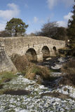 English river with old stone bridge on Dartmoor England UK. The East Dart River and road bridge built in the 1700`s at Postbridge on Dartmoor in Devon England UK stock photo
