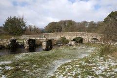 English river with old stone bridges on Dartmoor England UK. The East Dart River, the road bridge an the ancient clapper bridge at Postbridge on Dartmoor,Devon royalty free stock photos