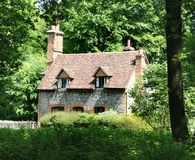 English Rural Cottage. Brick and Flint Cottage set in an English Woodland Royalty Free Stock Photo