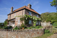 English Rural House and Garden with stone wall. English Rural House and garden with white Wisteria growing up the wall Royalty Free Stock Photos