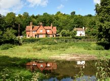English Rural Houses. Surrounded by Trees witha pond in the foreground showing their reflections Stock Image