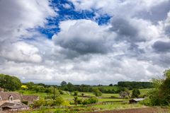 English rural landscape with dramatic sky over small village Sou. Summer english rural landscape with dramatic stormy sky over small village in Southern England Royalty Free Stock Photography