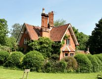 English Rural Lodge. English Red Brick Lodge House surrounded by a Shrub Hedge Royalty Free Stock Photos