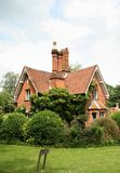 English Rural Lodge. English Red Brick Lodge House surrounded by a Shrub Hedge Stock Images