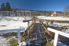 English rural village landscape in the winter. Landscape view of a rural english countryside village scene with traditional cottages and wooden footbridge over Royalty Free Stock Image