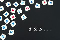 English colored square letters scattered on black background with numbers 123. English school concept, numbers 123, colored square english letters scattered on Royalty Free Stock Images