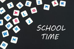 English colored square letters scattered on black background with text school time. English school concept, text school time, colored square english letters Royalty Free Stock Image
