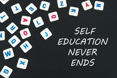 English colored square letters scattered on black background with text self education never ends. English school concept, text self education never ends, colored Royalty Free Stock Photos