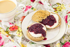 English scones with cream and strawberry jam. English scones  of whole wheat  with clotted cream and strawberry jam and tea Royalty Free Stock Photos
