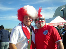 English soccer fans. Two dressed up English football fans with red and white wigs supporting England in the soccer world cup 2010 in South Africa Stock Photos
