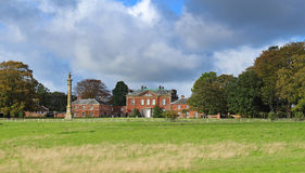 An English Stateley Home and garden. An English Stately Home with Monument viewed from the front Lawn Stock Image