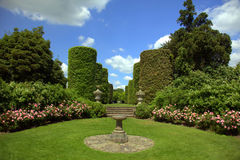 English stately home garden. Country garden with sundial and rose border with topiary shrubs and sundial Stock Image