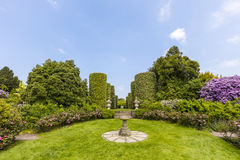 English stately home garden. Country garden with sundial and rose border with topiary shrubs and sundial Royalty Free Stock Image