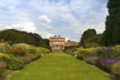 English stately home and gardens. Large lawn and herbaceous border with a mansion house Royalty Free Stock Image