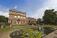 English stately home and gardens. Large old mansion house with landscaped gardens and a sculpture Stock Images