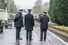 English steam trains and three conductors on the platform Stock Images